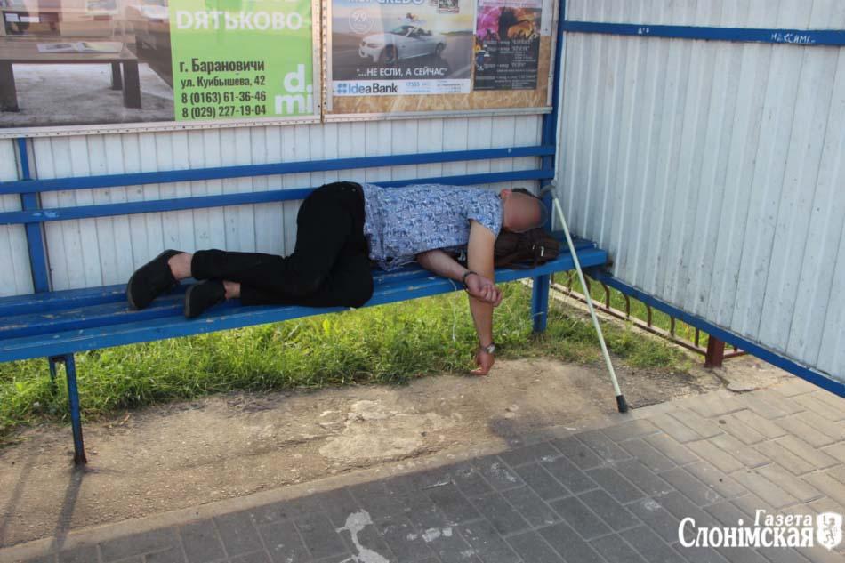 Лежащий на остановке человек с тросточкой